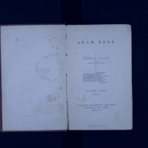 Open book showing front page. Text on right hand page is: Adam Bede by George Eliot. Author of Scenes of Clerical Life. This is followed by an extract by Wordsworth. Beneath is the text: In three volumes. Vol 1. William Blackwood & Sons, Edinburgh and London.