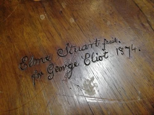Wood with the words Elma Stuart fecit for George Eliot 1874 carved into it.