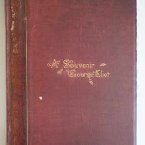 A book with a red cover. The words a Souvenir of George Eliot are written in gold in the centre.