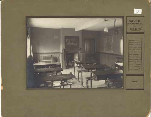 Black and white photograph of an old school room with tables and books underneath. The chalk board at the front has the words George Eliot's School room written on it. The title the old school room, the elms, Nuneaton is written on the right hand side of the green/brown mount.