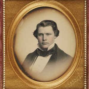 Black and white photograph of a man. The cheeks have been tinted pink. He has a high white collar, white shirt, black necktie and black jacket. The photograph is in an oval frame with a gold mount. It is in a red case.