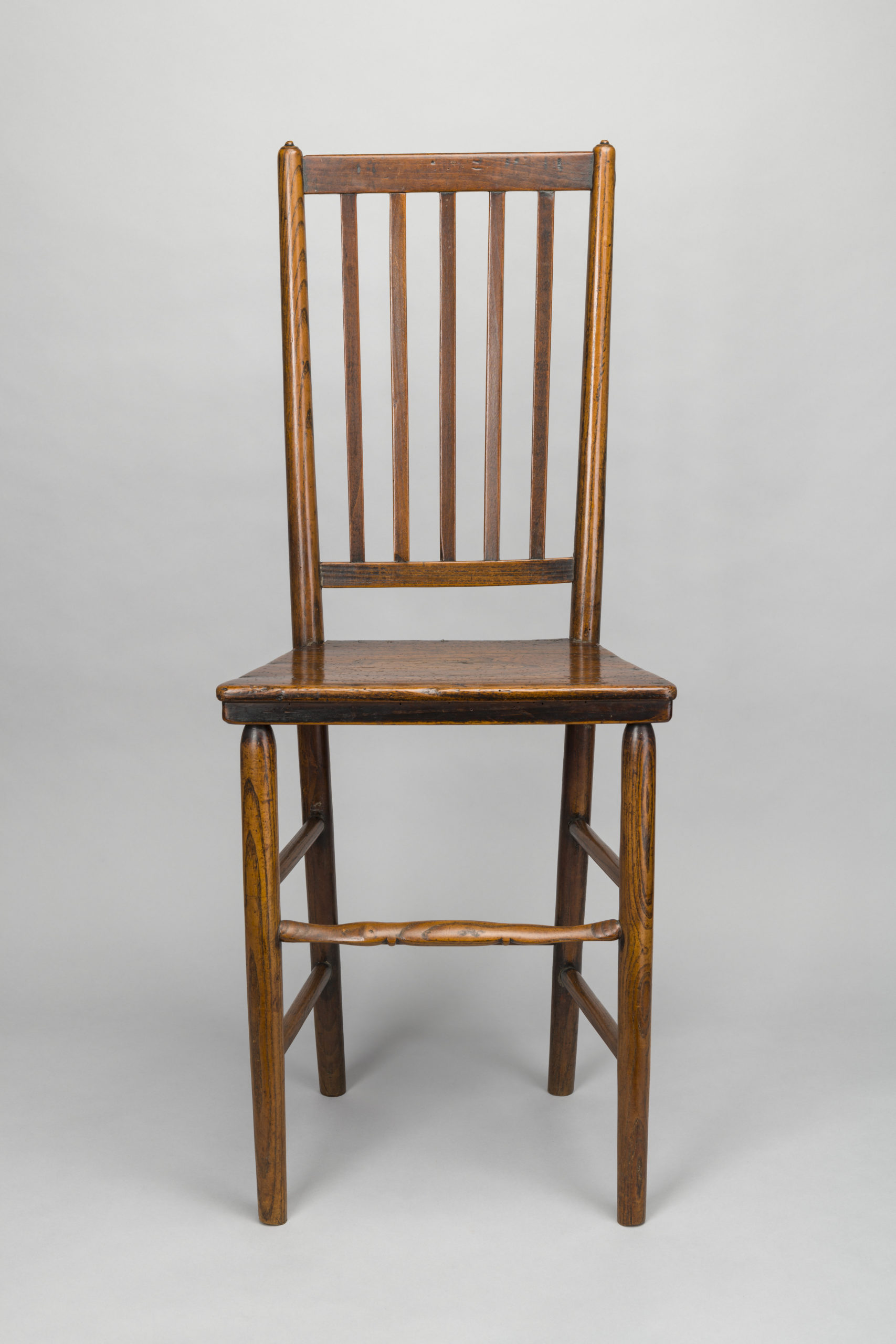 Photograph of a wooden chair with wooden spindles on the back of the chair.
