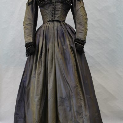 Mannequin displaying a blue floor length silk dress with long sleeves. The bodice has a square shaped black velvet trim. There is black bead trim round the neck following a black velvet trim. There is black velvet trim and lace at the wrists. There are buttons along the front to the waist.