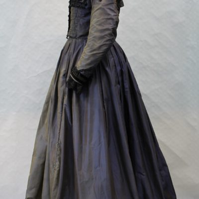Side view of a mannequin displaying a blue floor length silk dress with long sleeves. The bodice has a square shaped black velvet trim. There is black bead trim round the neck following a black velvet trim. There is black velvet trim and lace at the wrists. There are buttons along the front to the waist.