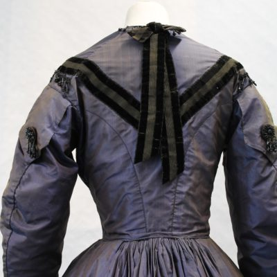 Bead trim round neck following velvet trim. Velvet trim and lace at wrists. Braid covered buttons Detail showing the back of a blue silk dress with long sleeves. The bodice has black velvet trim meeting at a point on the back and velvet tying at back of neck and running down back. There is black beading at the shoulders.