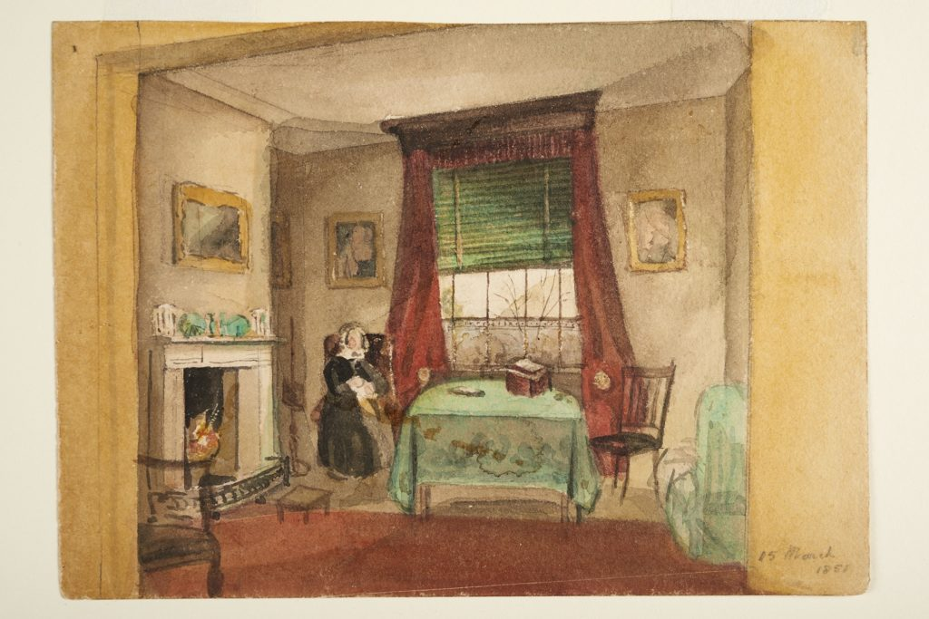 Painting of the interior of a room. There is a window in the background with a green blind half way down and red curtains. Figure sits in a chair in front of the window wearing a black dress and white bonnet. Next to the figure is a table covered in a green cloth and another chair. There are paintings on the walls and a fireplace on the left hand side.