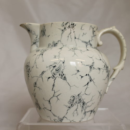 This is a photograph of a white jug with hndle on the right hand side. The jug is covered in blue lines.