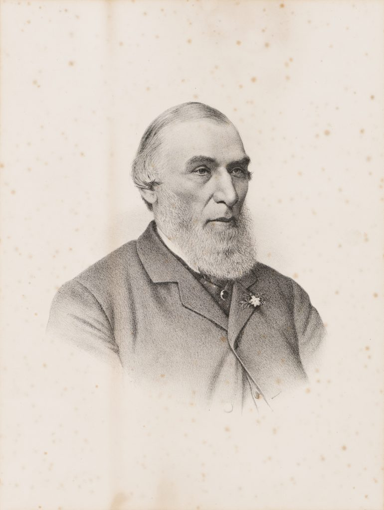Black and white portrait of a man. He has white hair and a beard. He is wearing a dark suit with a small flower in the capel. The jacket is fastened at the top button. Subject is wearing a necktie and a white collar shirt.