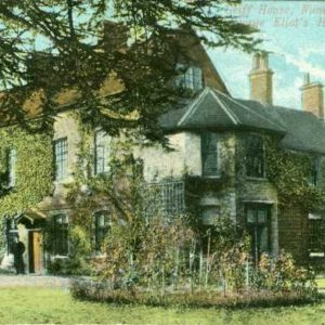 A colour postcard showing Griff House. A large house is shown. Ivy covers the walls. There is a garden in front of the house and a tree framing the house. A figure can be seen outside the front door. The words Griff House, Nuneaton. George Eliot's Home is written in the top right hand corner.
