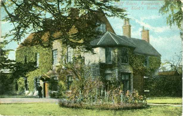 A colour postcard showing a large house. Ivy covers the walls. There is a garden in front of the house and a tree framing the house. A figure can be seen outside the front door. The words Griff House, Nuneaton. George Eliot's Home is written in the top right hand corner.