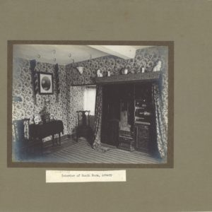 Black and white photograph showing the interior of a room. There is highly patterned wallpaper on the walls, A coal fire and oven can be seen on the right hand side. Above the very high fireplace are ornaments. There are two chairs and a table on the left hand side. Above this is a painting hanging on the wall. It is within a green/brown cardboard mount and the title Interior of South Farm, Arbury is typed on white paper beneath the photograph.