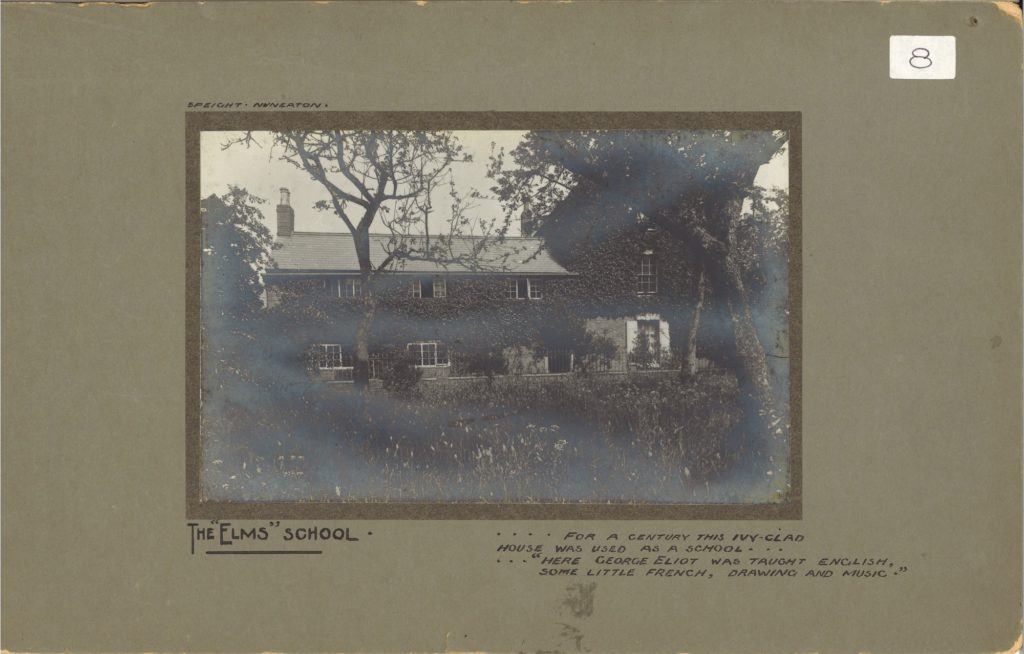 Black and white photograph showing a house whose wall are clad in ivy. Trees and bushes are all around the front of the building. Image is within a green/brown card mount. The words The Elms School are written on the mount.