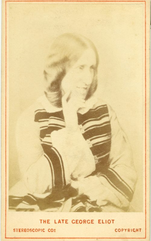 Black and white photograph showing George Eliot. She is turned slightly to one side and is resting her face lightly on her right hand. She is wearing a light coloured dress with dark stripes. The image has a red border and the words The Late George Eliot. Stereoscopic Co, Copyright are typed in red along the bottom.