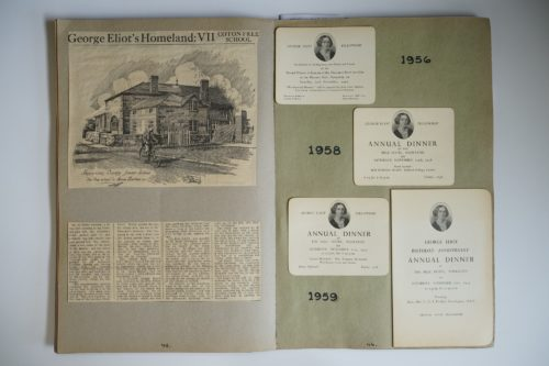 Open scrapbook. On the right hand side invitations and a programme for the George Eliot Fellowship Annual Dinner are stuck on the page with the date 1959 written onto the page. The left hand side has newspaper articles stuck onto the page