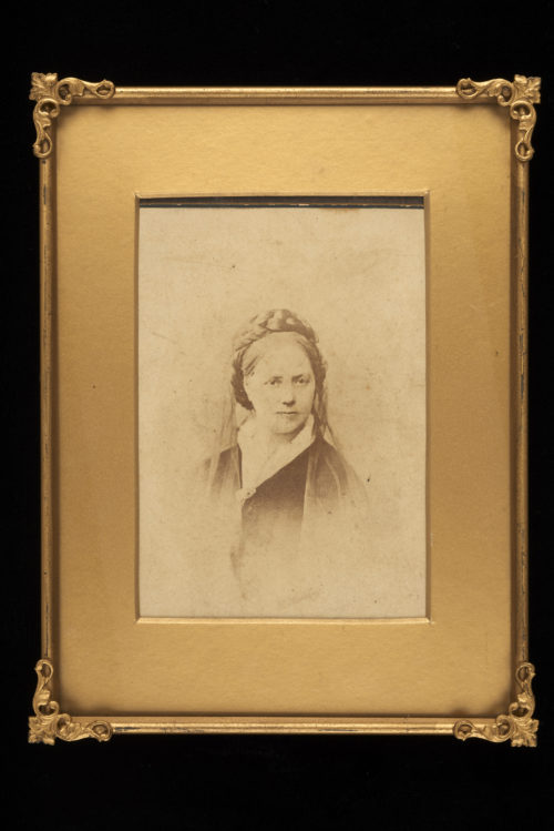 A black and white photograph of Rufa Hennell. It shows a woman whose hair is plaited around the top. There is a light veil around the back of her head. She is wearing a white collar and dark cloak or shawl fastened with a broach. The photograph as a gold border and frame.