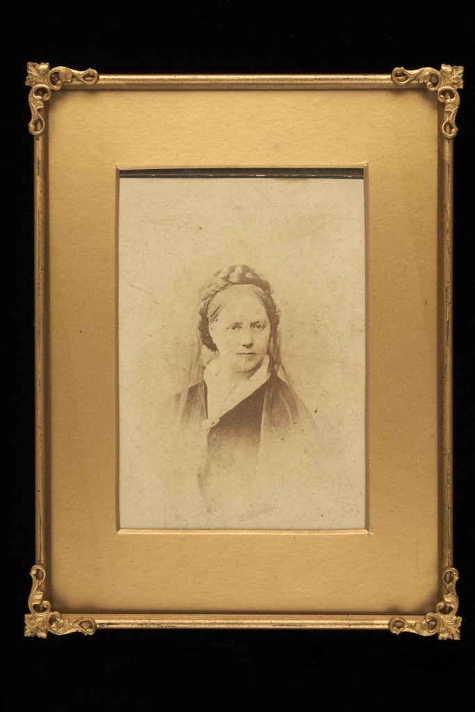 A black and white photograph of a woman. Her hair is plaited around the top. There is a light veil around the back of her head. She is wearing a white collar and dark cloak or shawl fastened with a broach. The photograph as a gold border and frame.