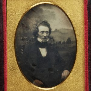 Black and white photograph of a seated man. He is wearing glasses, a white shirt and dark jacket. The photograph is in a gold mount and a red velvet cover.