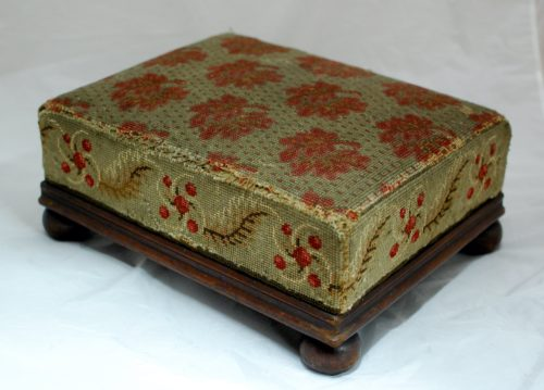 Wooden footstool with embroidered cushion. It is embroidered with a red flower pattern.