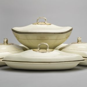 Side view of a supper set made up of one cream coloured boat shaped tureen on a stand. Three of the four dishes. All have lids decorated with a brown central circular leaf design and flowers on the handles.