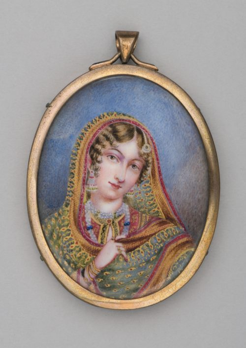 An oval shape pendant with a gold frame around a painting of a woman. She is wearing a highly patterned shawl which she holds with one hand. She is wearing earrings, necklaces and bracelets.