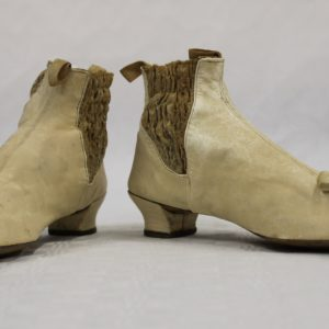 Two small cream coloured kid leather boots with silk cream bows near to the toe. They have a small heel. The sides have a darker band of smocking to allow easier fitting.