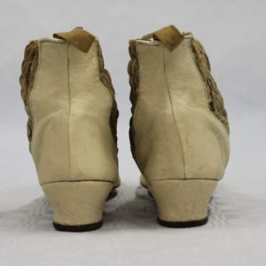 Back view of two small cream coloured kid leather boots. They have a small heel. The sides have a darker band of smocking to allow easier fitting.