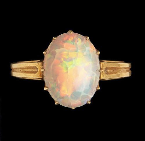Large gold ring set with a large opal. Photographed on a black background.