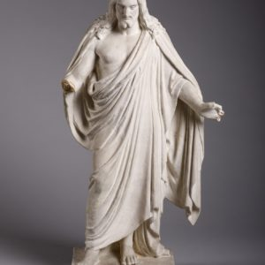 A small statue of a figure with long hair and arms slightly outstretched. The figure is wearing robes.