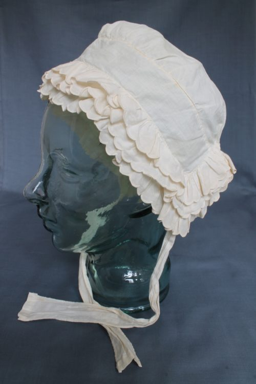 Side view of a white bonnet displayed on a clear mannequin. There are three rows of scalloped edged bands around the front and back. It has two lengths of cotton which would tie under the chin.
