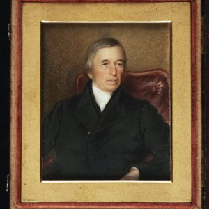 This is a miniature portrait painting inside a case, showing a man wearing a black coat and white cravat, seated with top portion of a red leather chair.
