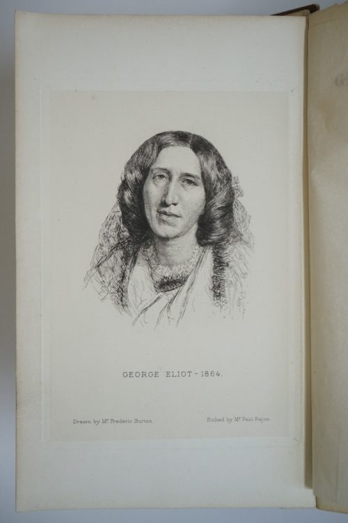 Inner page of a book showing the portrait of George Eliot. The words George Eliot - 1864. Drawn by Mr Frederic Burton. Etched by Mr Paul Rajon are typed underneath the portrait.
