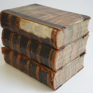 A stack of three books. There is damage to the spine of the top book revealing newspaper underneath. Cornhill Magazine is typed in gold on the spine of each book.