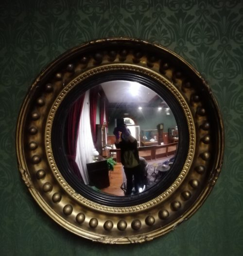 Circular mirror in ornate frame decorated with large spheres and leaves at the bottom, top and each side.