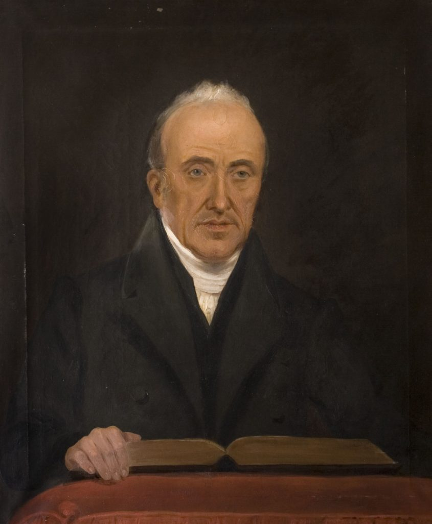 Painting of a man with white grey hair. He is wearing a white clerical collar and black robe. He is standing with one hand on a open book which is reading on a pedestal.