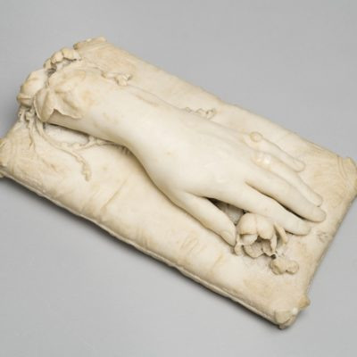 White marble sculpture of a hand and part of arm mounted on a rectangle marble cushion. Under the hand is a sculpted marble rose.