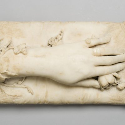 Surface view of a white marble sculpture of a hand resting on a marble cushion. Under the fingers is a marble rose.