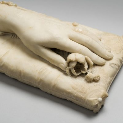 Detail of a white marble sculpture of a hand resting on a marble cushion. Under the finders a marble rose can be seen.