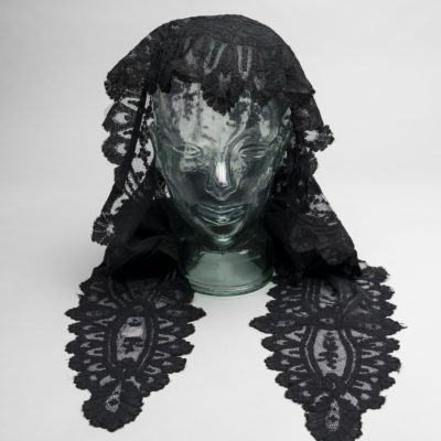 Black lace head shawl displayed on a glass mannequin. It covers the back of the head and has two long pieces on each side.