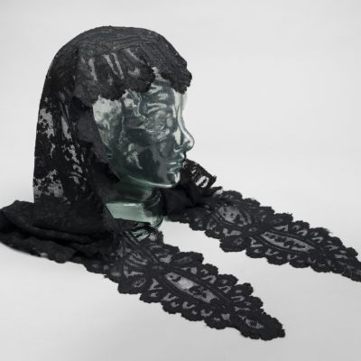 Side view of a black lace shawl. It covers the back of the head and has two long pieces on each side.