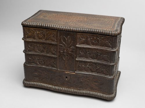 Intricately carved wooden box. It has four tiers which are all decorated with a carved floral design. The bottom tier appears to have a very small key hole.