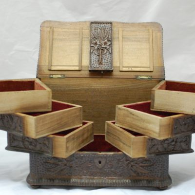 Open view of a wooden lace box. The open lid is of page wood with a dark wood decorated panel in the centre. There are three stacked compartments on the left and right which are lined with a red material.. The centre provides a large storing space.