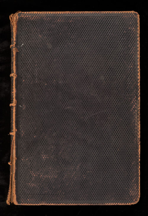 Front cover of a large book. Black with a diamond criss-cross pattern. Tan edges show signs of wear.
